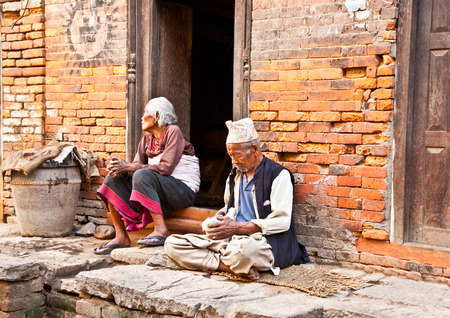 BHAKTAPUR,NEPAL-MAY 20:Old woman and man sitting intertwined their homes on May 20, 2013, Bhaktapur,Nepal.Bhaktapur is one of 3 Royal cities in the Kathmandu Valley and considered a cultural gem. 2013