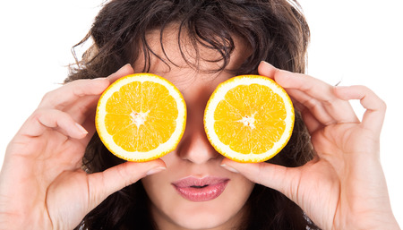 Portrait of young cheerful woman with two slices of orange Standard-Bild - 120897608