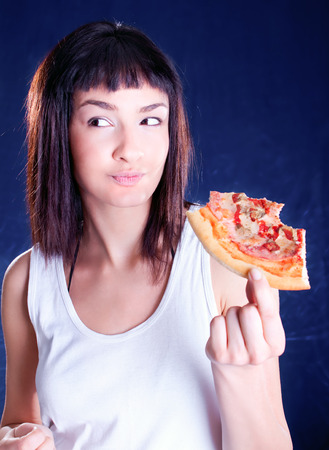 Young happy woman eating pizza, isolated on dark Banco de Imagens - 120897689