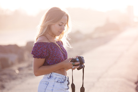 Young woman checks her camera after taking pictures on the beach