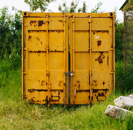 locked: the  locked yellow container on grass Stock Photo