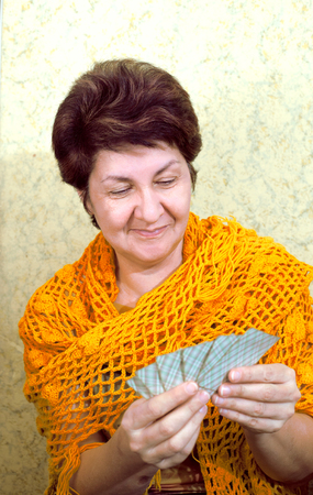 Woman smiling, looking at playing cards Stock Photo