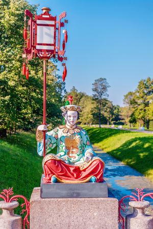 Statue of the Chinese woman sitting on a pedestal with a big lamp on a pole. Russia, Saint-Petersburg, Tsarskoye Selo.