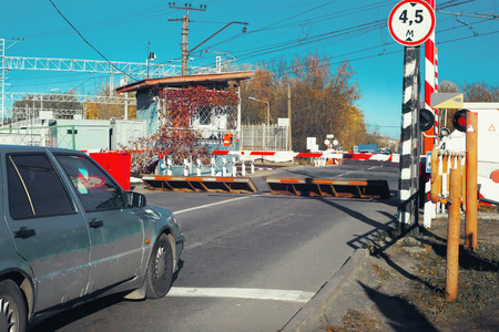 Railway crossing with lowered turnpike and raised barriers of protection devices against RAM