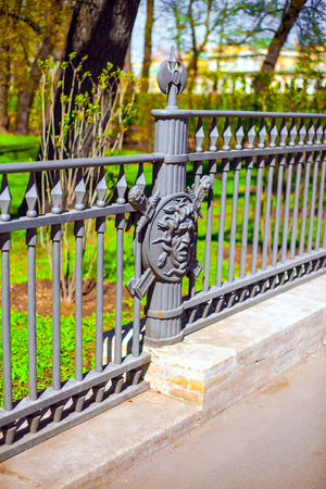 A fragment of the metal fence of the Summer garden in St. Petersburg decorated with the image of the face of Medusa Gorgon on the background of a shield and swords