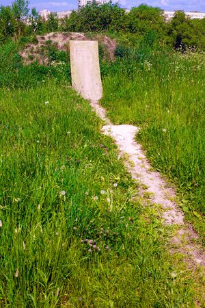 A steep springboard and a track to it at the site for testing bicycles in the thickets of grass Stock Photo