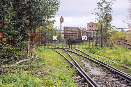 The the railway track abuts against closed lattice metal gates, behind which the rails diverge in two different directions
