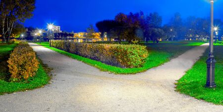The route in the park at night is divided into two alleys, diverging in different directions Stock Photo