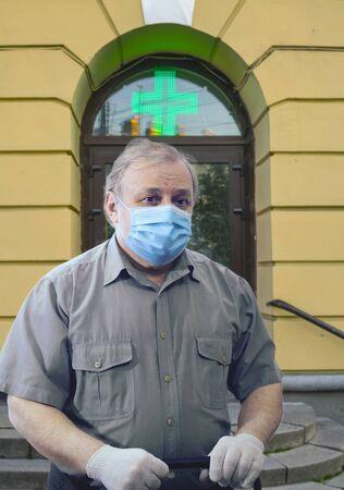 Sad elderly man wearing medical mask and white gloves stands near hospital entrance