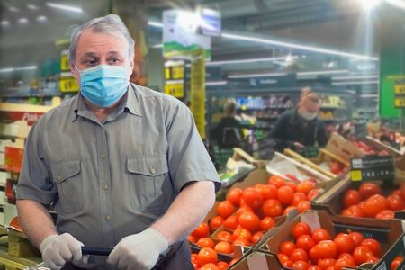 An elderly man in a short-sleeve shirt, medical mask and white gloves stands near boxes with red tomatoes in the market.