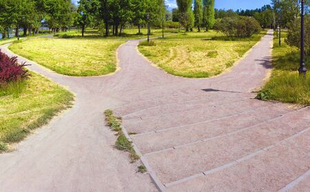The wide road is divided into three alleys in the park, going in different directions. Conceptual summer landscape