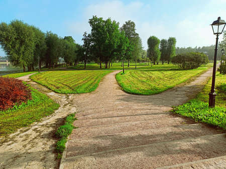 In the park near the river, a wide road is divided into three alleys going in different directions. Conceptual summer landscape Stock Photo