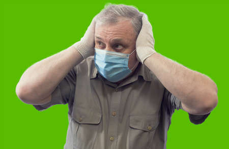 A man wearing a short sleeved shirt, a medical mask and gloves, clutching his head anxiously, horizontal portrait isolated on a green background.