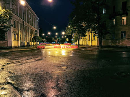 The exit road from the asphalt area is blocked by plastic barriers and road signs. Night cityscape