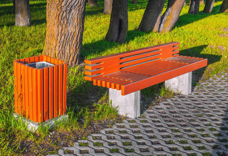 New orange bench and urn in the sun near the sidewalk, green grass and tree trunks