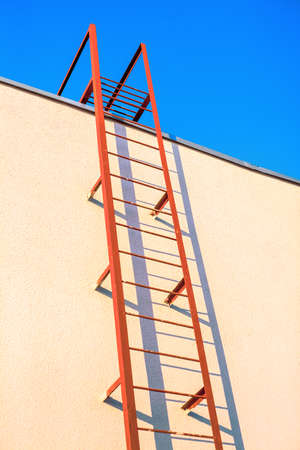 The way up. A painted metal steep staircase leads up the wall to the upper landing.