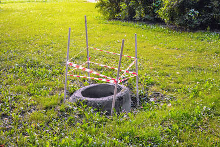 A round, uncovered sewer pit is fenced off for safety with warning tape on wooden posts Stockfoto