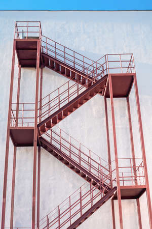 Exterior brown painted metal fire escape on the wall of a multi-storey building