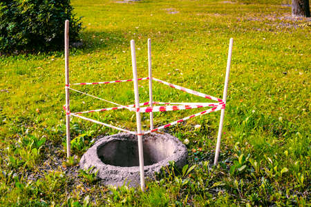 A round open sewer pit among the grass is fenced with warning tape on wooden posts for safety.