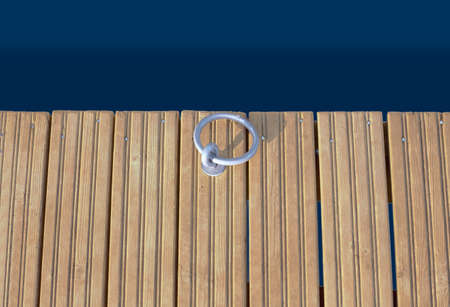 Large mooring metal ring for fixing the vessel, fixed on the edge of a wooden pier above dark water, top view