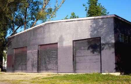 Facade of a large dark hangar building with three closed doorways