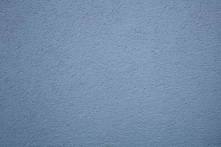 A simple texture of blue-gray background in the form of a rough grainy coating with putty or plaster on a flat surface