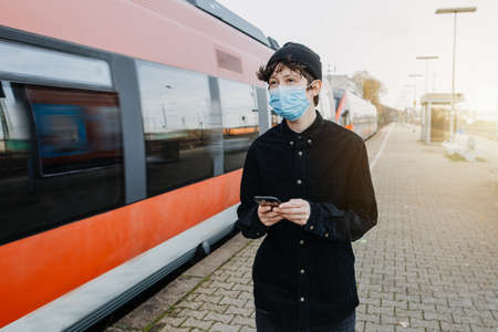 Coronavirus, COVID-19. Young German man with medical face mask to protect against the coronavirus while waiting for the train on the subway platform. Mouth protection obligation at the train station