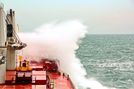 Movement of the vessel in stormy weather, Pacific Ocean. Waves and spray covering the ship during a storm