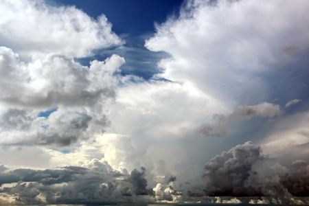 The clouds are multicolored, thunderous bizarre shapes against the blue sky and the sun above the ocean surface. The game of light and shadows in various variations of sunlight illumination of clouds and sky. Archivio Fotografico