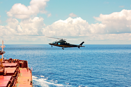 Helicopter as the main means of landing and acceptance of sea pilots for sea vessels in Australian waters, 2018. View of a helicopter close-up against a blue sky and a sea ship. 版權商用圖片