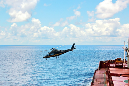 Helicopter as the main means of landing and acceptance of sea pilots for sea vessels in Australian waters, 2018. View of a helicopter close-up against a blue sky and a sea ship. Stock Photo