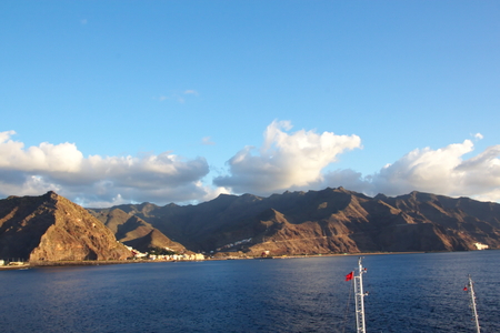 Colorful view of the coast of the Canary Islands and the port of Las Palmas against the blue sky and clouds from the side of the sea ship anchored. February, 2012.