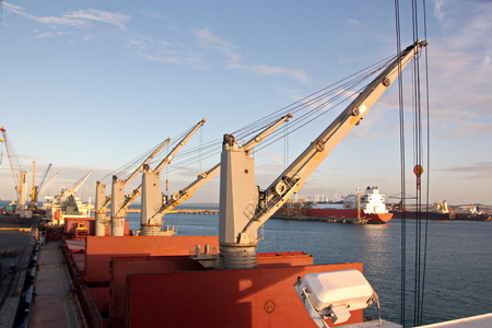 Transshipment terminal for loading steel products to sea vessels using shore cranes and special equipment. Vessels moored at berths and anchored in the roadstead. Sea and coastal line. Port Pecem, Brazil, June, 2017.
