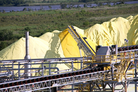 Transhipment terminal for loading bulk cargo of chemical sulphur to sea bulk carriers using a shore crane. Port Beaumont, Texas, USA. July, 2017. Stock Photo
