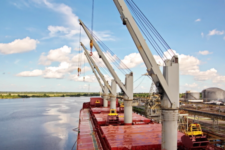 Transhipment terminal for loading bulk cargo of chemical sulphur to sea bulk carriers using a shore crane. Port Beaumont, Texas, USA. July, 2017. Фото со стока