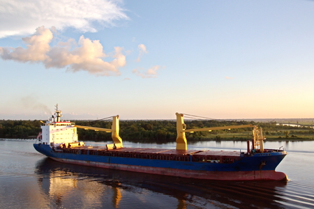 The movement of sea merchant ships and tugs to the entrance and exit from the port. View of the river Neches. Port Beaumont, Texas, USA. July 2017.
