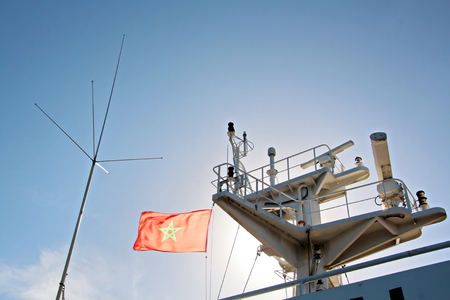 State flags raised on the mast of a merchant ship in the ports of call. Different kinds of flags against the blue sky and clouds. Stock Photo