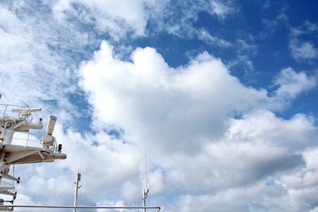 Ship structures, masts, antennas, funnel, ship wheelhouse against the blue sky and clouds. Stock Photo