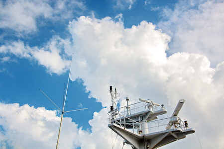 Ship structures, masts, antennas, funnel, ship wheelhouse against the blue sky and clouds. Stock Photo - 108603165