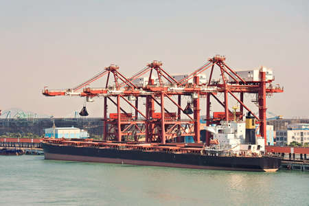 Type of cargo terminal and cranes, berths for transshipment of bulk cargo, iron ore and coal. Port Zhuhai, China.