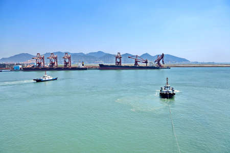 Cargo terminal for transshipment of bulk cargo, iron ore and coal. Bulk carrier movement using tugboats, departure from the port Zhuhai, China.