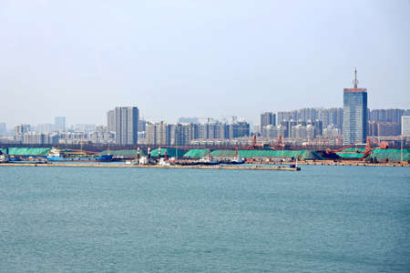 Panoramic views of piers, sea vessels, tugboats and the city of Rizhao, China