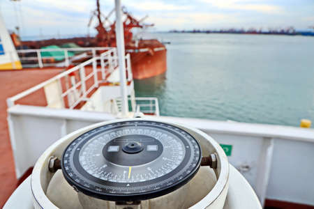 View of the ship and piers on the background of the magnetic compass card. Stock Photo