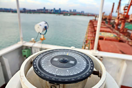 View of the ship and piers on the background of the magnetic compass card.