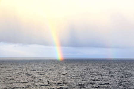 Rainbow in the ocean after rain and thunderstorm. North Pacific Ocean. Archivio Fotografico