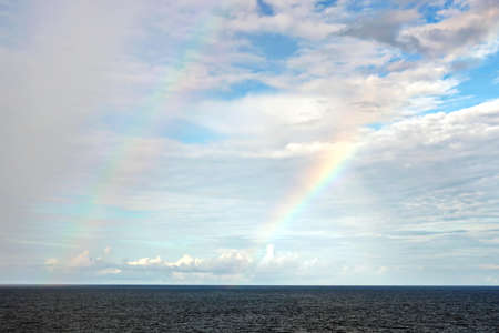 Rainbow in the ocean after rain and thunderstorm. North Pacific Ocean.