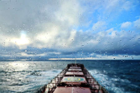 View of the ocean and sky through raindrops on the glass of a ship's porthole.