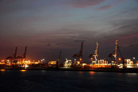 Night views of ships and berths in the port. Colorful views, the play of colors at sunset. Port Jeddah, Saudi Arabia. December, 2018