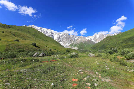Landscape views of the Caucasus Mountains, river and villages. Peak and river Enguri. Georgia. Summer. 2019