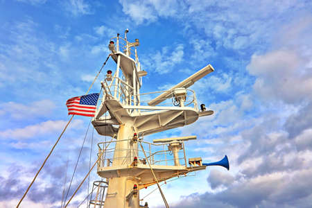 Ship structures, masts, antennas, funnel, ship wheelhouse against the blue sky and clouds.